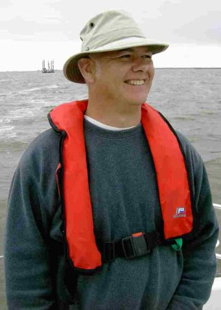 Image of Andy Spong in lifejacket and hat, sailing in Holland.